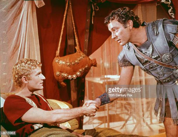 Welshborn actor Richard Burton as Marc Antony shakes hands with British actor Roddy McDowall as Caesar Augustus in a still from the film 'Cleopatra'...