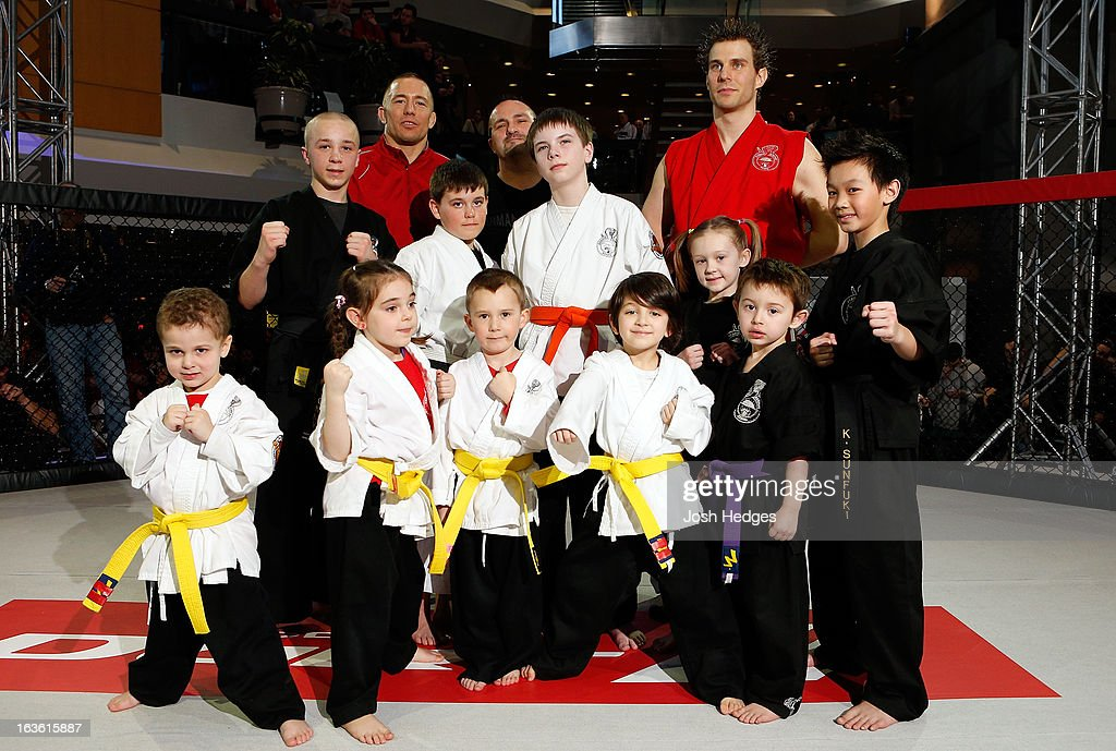 UFC welterweight champion Georges St-Pierre poses for photos with students of the Sunfuki Karate school during the UFC 158 open workouts at Complexe Desjardins on March 13, 2013 in Montreal, Quebec, Canada.