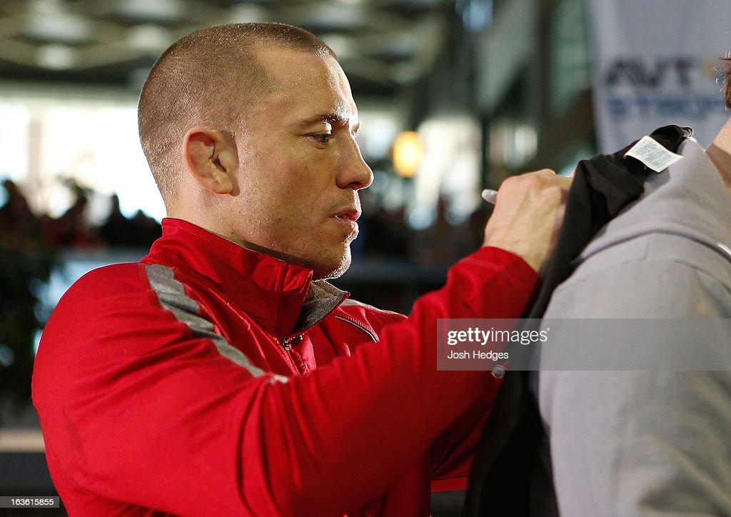 UFC welterweight champion <a gi-track='captionPersonalityLinkClicked' href=/galleries/search?phrase=Georges+St-Pierre&family=editorial&specificpeople=4864241 ng-click='$event.stopPropagation()'>Georges St-Pierre</a> signs autographs for fans in attendance during the UFC 158 open workouts at Complexe Desjardins on March 13, 2013 in Montreal, Quebec, Canada.