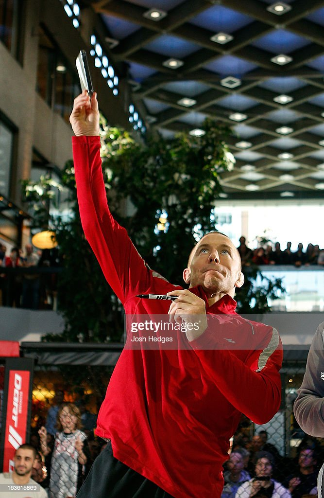 UFC welterweight champion Georges St-Pierre tosses autographed DVD's into the crowd during the UFC 158 open workouts at Complexe Desjardins on March 13, 2013 in Montreal, Quebec, Canada.