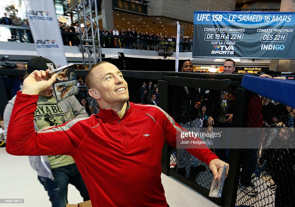 UFC welterweight champion <a gi-track='captionPersonalityLinkClicked' href=/galleries/search?phrase=Georges+St-Pierre&family=editorial&specificpeople=4864241 ng-click='$event.stopPropagation()'>Georges St-Pierre</a> tosses autographed DVD's into the crowd during the UFC 158 open workouts at Complexe Desjardins on March 13, 2013 in Montreal, Quebec, Canada.