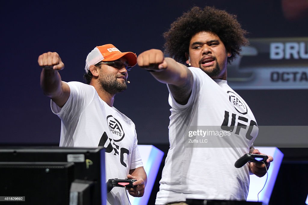 UFC welterweight champion Johny Hendricks interacts with a fan while playing the new EA Sports UFC game on the main stage during the UFC Fan Expo...