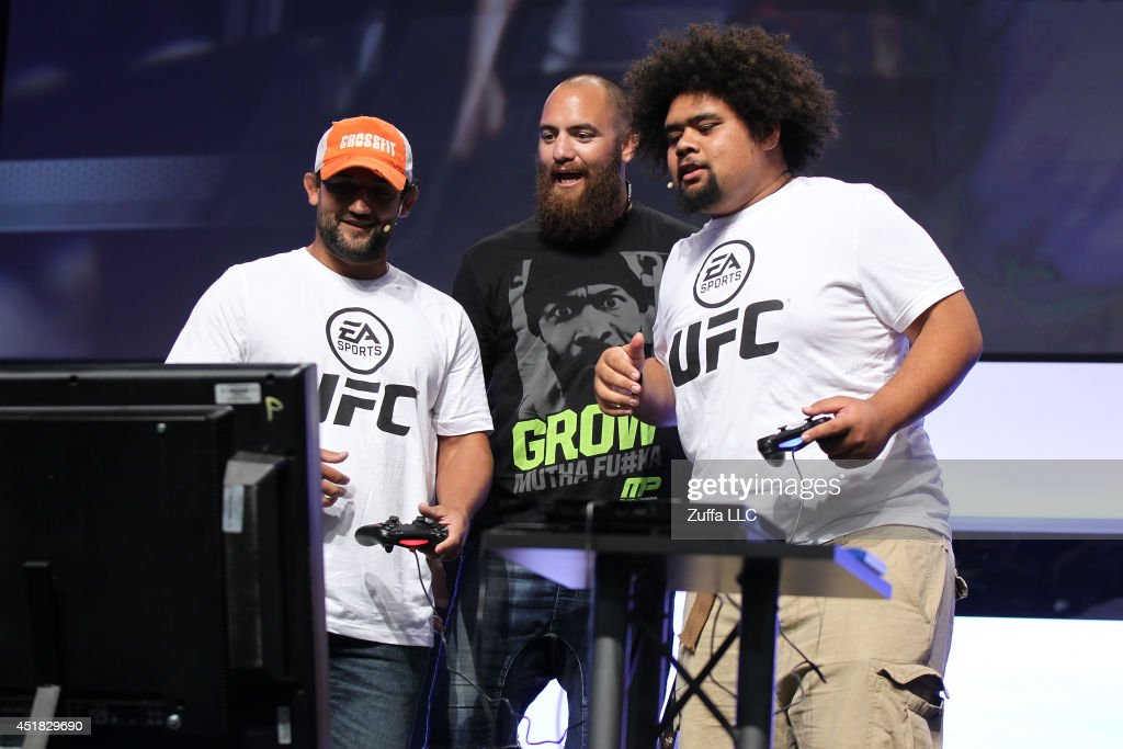 UFC welterweight champion Johny Hendricks interacts with Travis Browne and a fan while playing the new EA Sports UFC game on the main stage during...