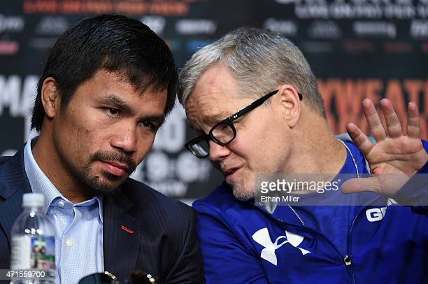 WBO welterweight champion Manny Pacquiao talks with his trainer Freddie Roach during a news conference at the KA Theatre at MGM Grand Hotel Casino on...