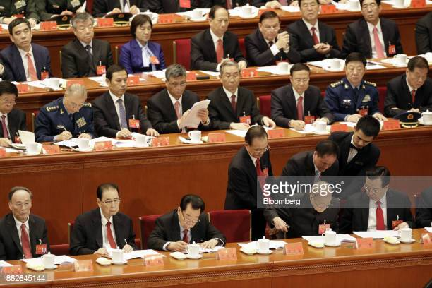 Wen Jiabao China's former premier center right and attendants assist Song Ping former member of China's Poliburo Standing Committee at his seat as...