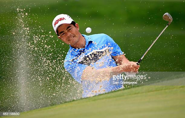 Wenchong Liang of China plays a shot from a bunker on the 13th hole during the first round of the World Golf Championships Bridgestone Invitational...