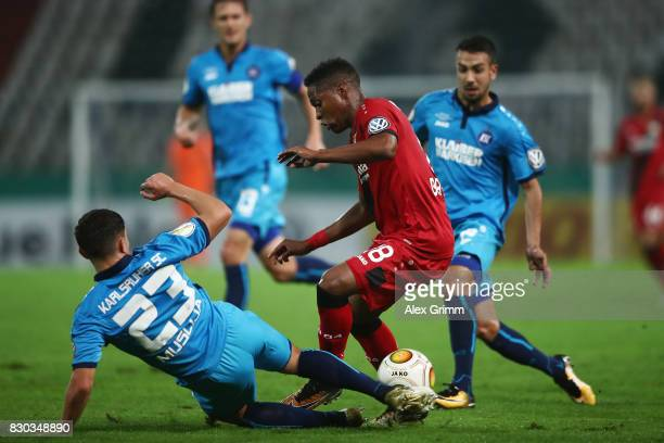 Wendell of Leverkusen is challenged by Florent Muslija lkaa during the DFB Cup first round match between Karlsruher SC and Bayer Leverkusen at...