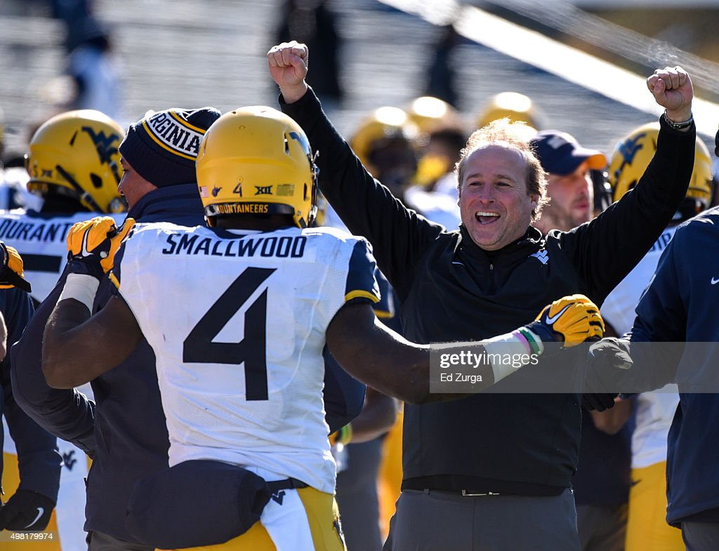 Wendell Smallwood of the West Virginia Mountaineers celebrates his 24yard touchdown run with head coach Dana Holgorsen in the first quarter against...