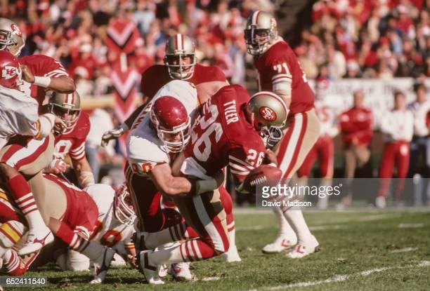 Wendell Tyler of the San Francisco 49ers fumbles the ball while being hit by Bob Hamm of the Kansas City Chiefs during a National Football League...