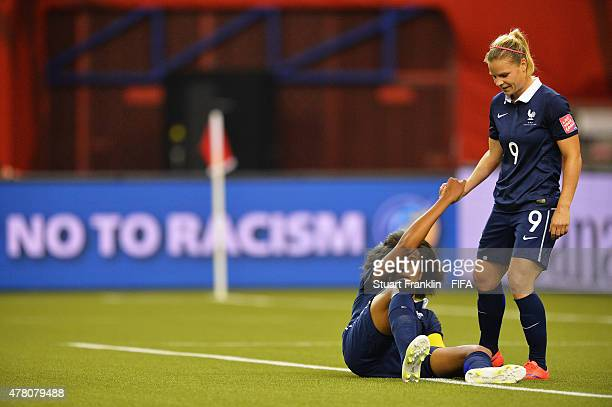Wendie Renard of France is helped by Amandine Henry during the FIFA Womens's World Cup round of 16 match between France and Korea at Olympic Stadium...