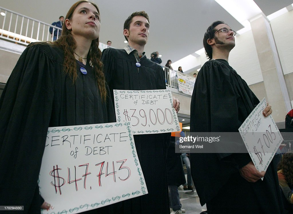 Wendy Crolla Christopher Collins 25 and Chris Wagner 25 each recieved their certificate of debt at a mock graduation as part of a protest at Sidney...