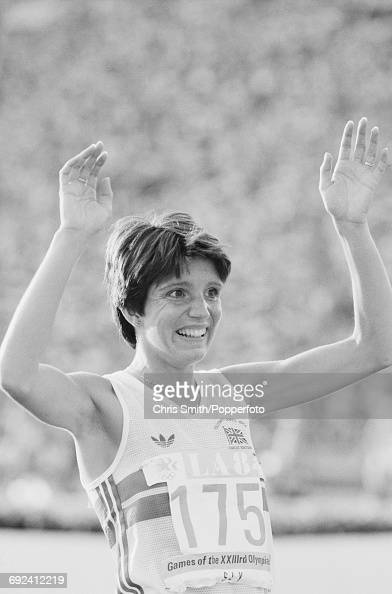 Wendy Sly of Great Britain raises her arms in the air as she finishes in second place to win the silver medal in the final of the Women's 3000 metres...