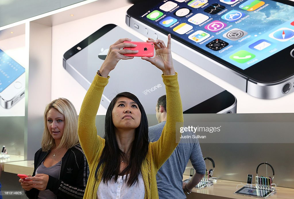 Wendy Sudsinsunthorn takes a picture with the new Apple iPhone 5C at an Apple Store on September 20, 2013 in Palo Alto, California. Apple launched two new models of iPhone: the iPhone 5S, which is preceded by the iPhone 5, and a cheaper, paired down version, the iPhone 5C. The phones come with a new operating system.