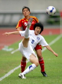 Weng Xinzhi of China vies with Han Song I of Korea during the friendship match between China national women's soccer team and Korea in Hangzhou on...