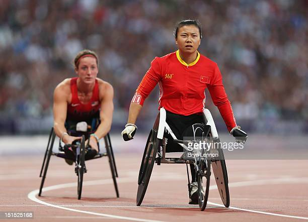Wenju Liu of China crosses the line to win gold ahead of bronze medallist Tatyana Mcfadden of the United States in the Women's 100m T54 Final on day...