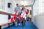 Parents and students walking down a primary school corridor. the parents are looking at some paperwork and the children are talking.