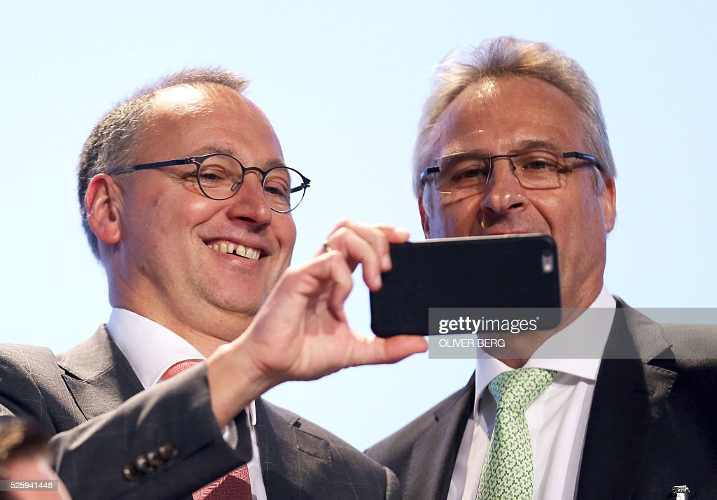 Werner Baumann (L), designated CEO of German chemicals and pharmaceuticals giant Bayer, watches a mobile device with board member Hartmut Klusik during their company's annual general meeting on April 29, 2016 in Cologne, western Germany. / AFP / dpa / Oliver Berg / Germany OUT