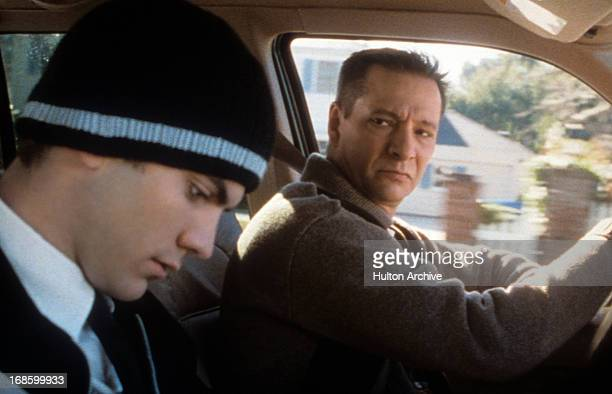 Wes Bentley wearing a sweater cap and sitting in the passenger seat of a car next to Chris Cooper in a scene from the film 'American Beauty' 1999