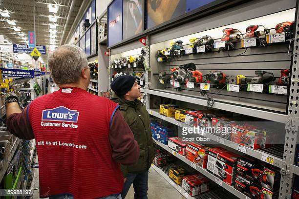 Wes Bielinski helps a customer shop for a sander at a Lowe's home improvement store on January 24 2013 in Chicago Illinois Lowe's said they plan to...