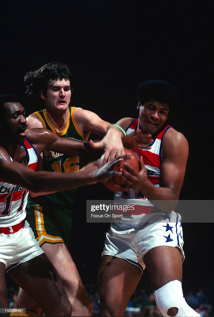 Wes Unseld and Elvin Hayes of the Capital Bullets fights for a rebound with Tom Burleson of the Seattle Supersonics during an NBA basketball game...