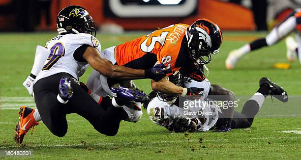 Wes Welker of the Denver Broncos is tackled by Michael Huff of the Baltimore Ravens during the third quarter of the game at Sports Authority Field at...