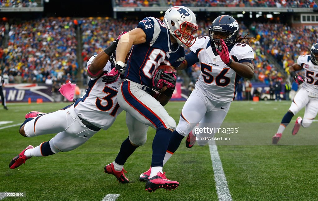 Wes Welker #83 of the New England Patriots runs with the ball on a punt return in front of Omar Bolden #31 and Nate Irving #56 of the Denver Broncos during the game on October 7, 2012 at Gillette Stadium in Foxboro, Massachusetts.