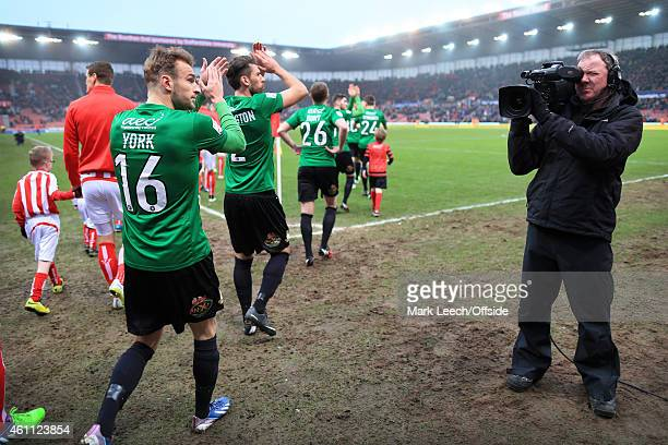 Wes York of Wrexham applauds the support as he emerges onto the pitch in front of a television cameraman for the FA Cup Third Round match between...