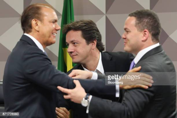 Wesley Batista former chief executive officer of JBS SA center stands while Senator Ataides Oliveira left greets Ticiano Figueiredo attorney for...