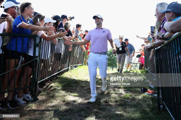Wesley Bryan of the United States high fives fans after putting on the ninth green during the first round of the Travelers Championship at TPC River...