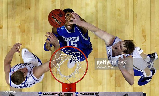 Wesley Dunning of the Hampton Pirates grabs a rebound between Mason Plumlee and Kyle Singler of the Duke Blue Devils during the second round of the...