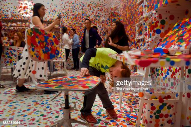 Wesley Horner looks for a unique place to apply what remains of his stickers as the last visitors apply the final dots to the Obliteration Room on...
