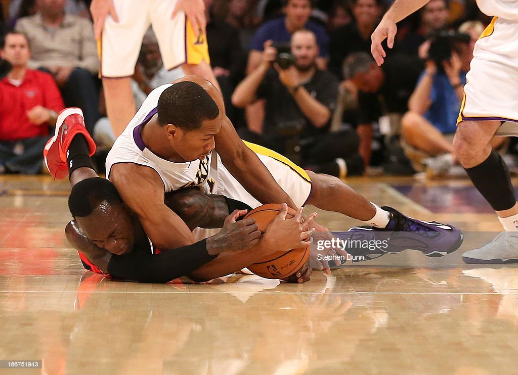 Wesley Johnson #11 of the Los Angeles Lakers and Dennis Schroder #17 of the Atlanta Hawks dive for a loose ball at Staples Center on November 3, 2013 in Los Angeles, California.