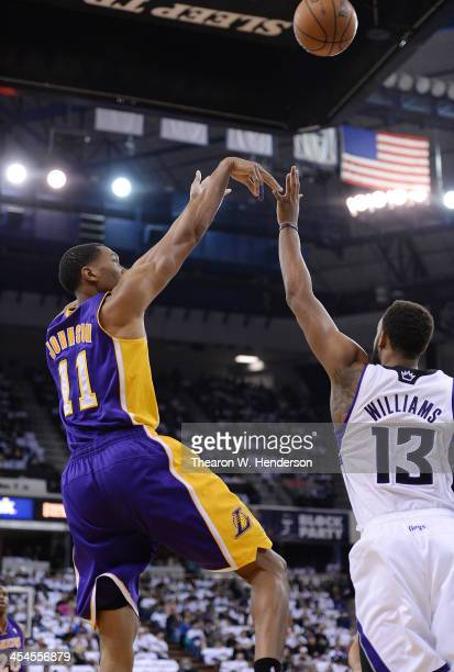 Wesley Johnson of the Los Angeles Lakers shoots over Derrick Williams of the Sacramento Kings at Sleep Train Arena on December 6 2013 in Sacramento...