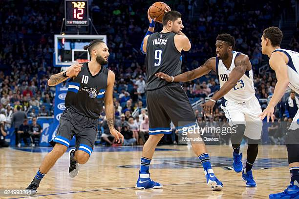 Wesley Matthews of the Dallas Mavericks guards Nikola Vucevic and Evan Fournier of the Orlando Magic at Amway Center on November 19 2016 in Orlando...