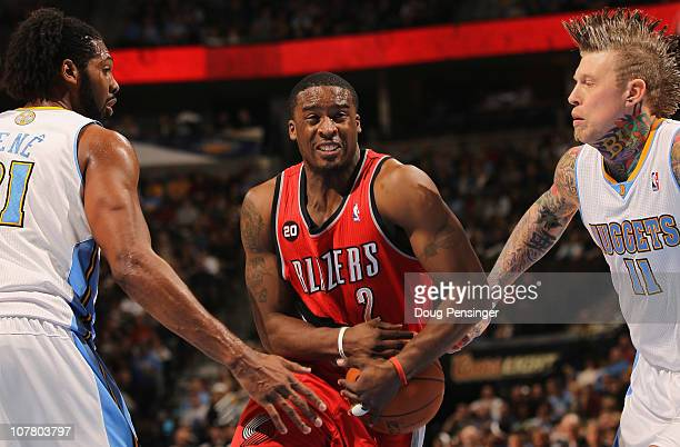 Wesley Matthews of the Portland Trail Blazers tries to hang onto the ball as he drives between Nene and Chris Andersen of the Denver Nuggets at Pepsi...
