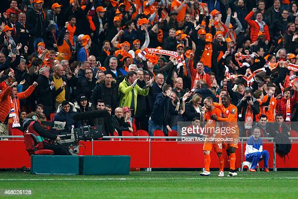 Wesley Sneijder and Jetro Willems of Netherlands celebrate the goal in the final minutes by Klaas Jan Huntelaar as the home fans cheer during the...