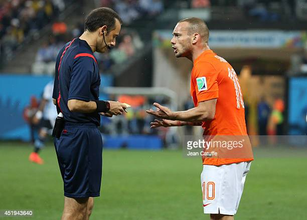 Wesley Sneijder of the Netherlands argues with Turkish referee Cuneyt Cakir during the 2014 FIFA World Cup Brazil Semi Final match between the...
