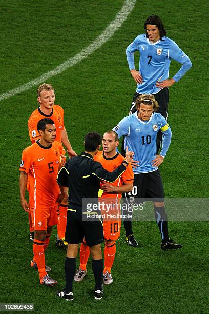 Wesley Sneijder of the Netherlands is shown a yellow card by referee Ravshan Irmatov after Martin Caceres of Uruguay accidently kicks Demy De Zeeuw...