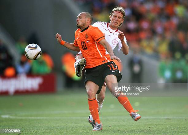 Wesley Sneijder of the Netherlands is tackled by Christian Poulsen of Denmark during the 2010 FIFA World Cup Group E match between Netherlands and...