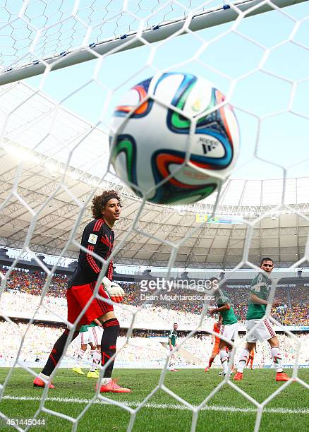 Wesley Sneijder of the Netherlands scores his team's first goal past Guillermo Ochoa of Mexico during the 2014 FIFA World Cup Brazil Round of 16...