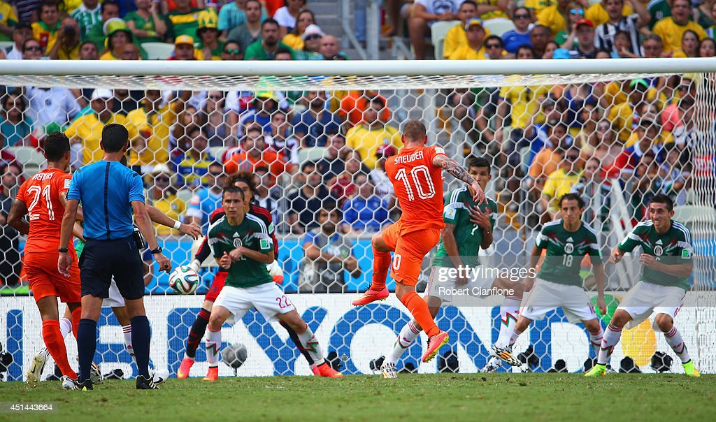 Wesley Sneijder of the Netherlands shoots and scores his team's first goal past Guillermo Ochoa of Mexico during the 2014 FIFA World Cup Brazil Round of 16 match between Netherlands and Mexico at Castelao on June 29, 2014 in Fortaleza, Brazil.