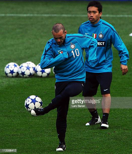 Wesley Sneijder plays with the ball next to team mate Yuto Nagatomo during a Inter Milan training session ahead of the UEFA Champions League quarter...