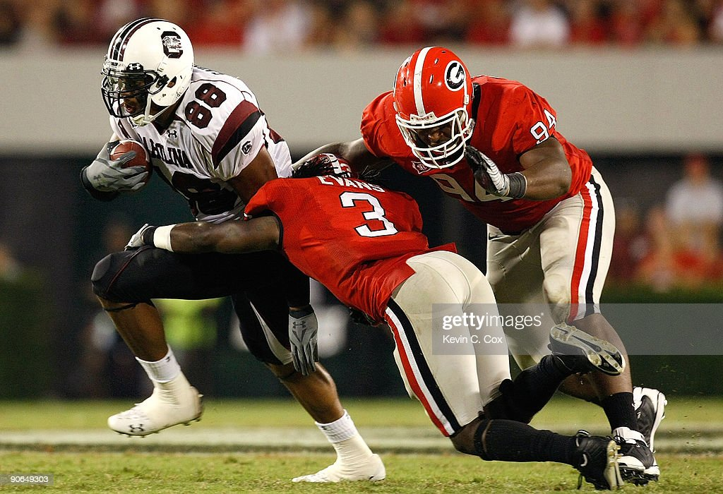 Weslye Saunders of the South Carolina Gamecocks breaks a tackle by Bryan Evans and DeAngelo Tyson of the Georgia Bulldogs at Sanford Stadium on...