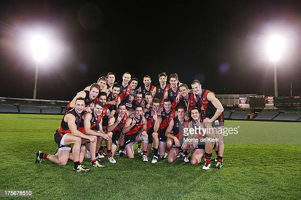 West Adelaide players celebrate with the trophy after winning the Foxtel Cup Grand Final between West Adelaide and East Fremantle at AAMI Stadium on...