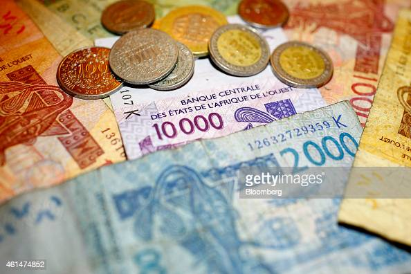 West African CFA franc currency banknotes and coins sit in this arranged photograph in Dakar Senegal on Sunday Jan 11 2015 Dakar with 3 million...