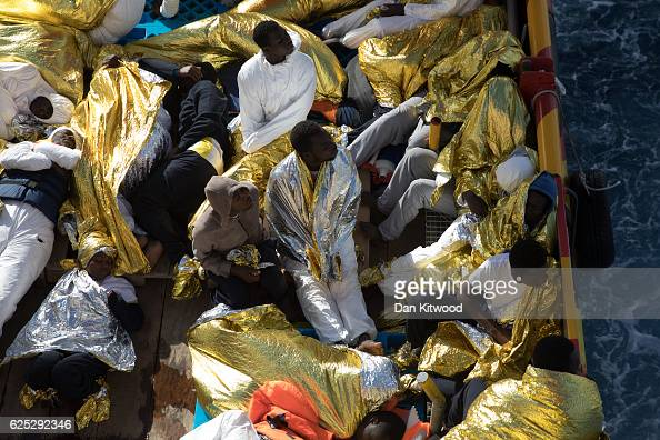 West African men relax on the deck of the Topaz Responder MOAS' Migrant Offshore Aid Station search and rescue vessel as it makes its way to Vibo...