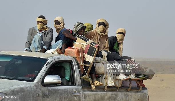 West African migrants returning from Libya sit in a pickup truck with their belongings in Agadez northern Niger on May 30 2015 AFP PHOTO / ISSOUF...