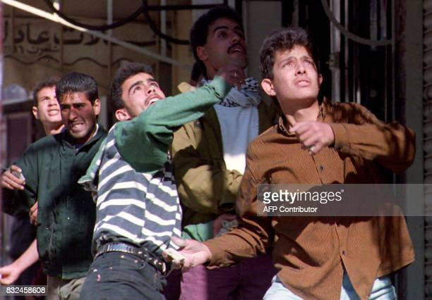 Palestinian youths throw stones at Israeli forces during yet another series of clashes that erupted 10 December 1993 following the killing by a...