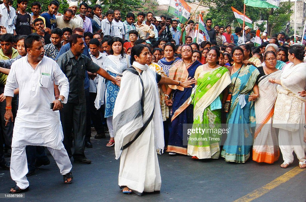 West Bengal Chief Minister and TMC chief <a gi-track='captionPersonalityLinkClicked' href=/galleries/search?phrase=Mamata+Banerjee&family=editorial&specificpeople=585449 ng-click='$event.stopPropagation()'>Mamata Banerjee</a> along with Railway Minister Mukul Roy attend a protest rally at South Kolkata on May 26, 2012 in Kolkata, India. Trinamool Congress workers carried posters demanding that the hike in petrol price be rolled back and shouted slogans against the UPA government's decision.