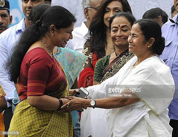 West Bengal Chief Minister Mamata Banerjee with DMK leader Kanimozhi Karunanidhi during her swearingin ceremony at Red Road on May 27 2016 in Kolkata...